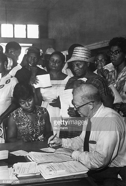 1/15/1966Canton Mississippi Federal voter registrar Louis Searson fills out a form for a prospective Negro voter as others wait their turn The...