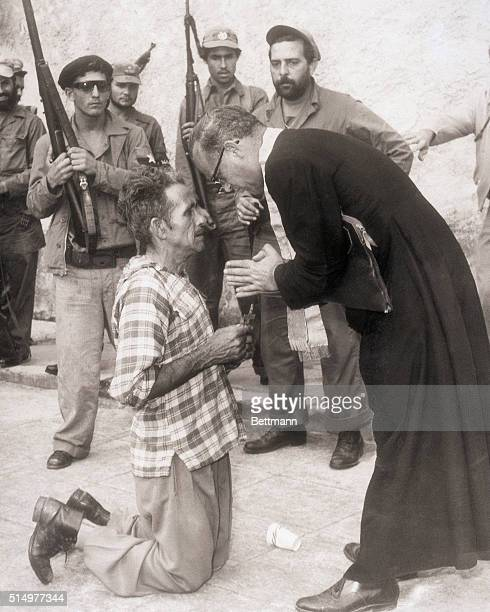 1/17/1959Matanzas Cuba In this Pulitzer prize winning photo Corporal Jose Cipriano Rodriguez holds a crucifix as he kneels before Father Domingo...