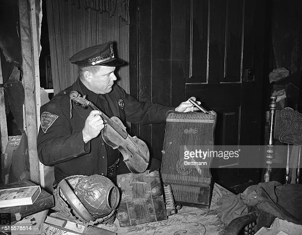 1/19/1957Plainfield WI Trooper Dave Sharkey looks over some of the musical instruments found in the home of bachelor farmer Ed Gein suspected grave...
