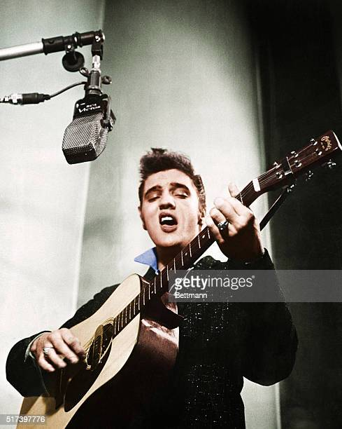Close up of Elvis Presley playing guitar.