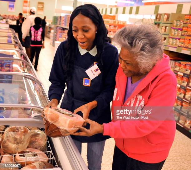 Aldi's cashier Davetta Coates talked with neighborhood resident Flossie Calvin as she looked at the hams as she toured the new grocery store as part...