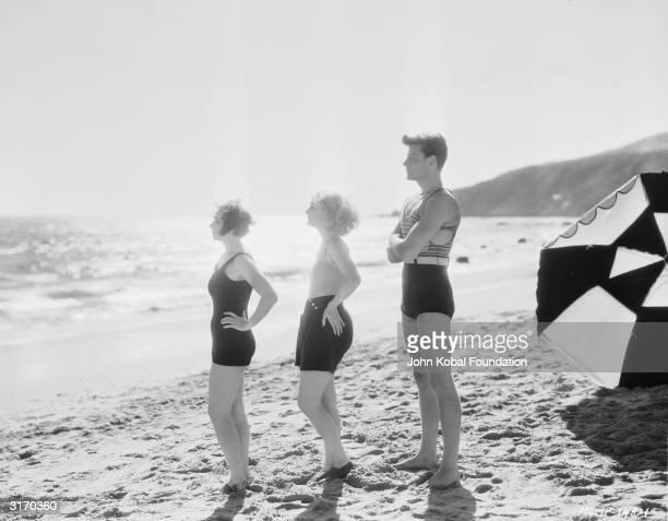 American actor Joel McCrea on the beach with two sunbathing beauties.