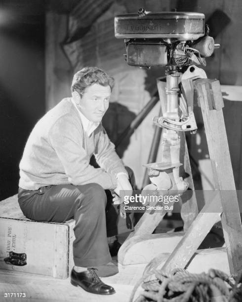 American actor Spencer Tracy sitting by an outboard motor.
