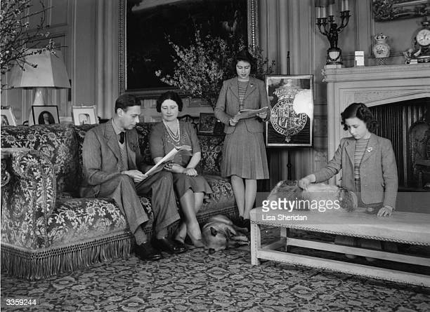 King George VI and Queen Elizabeth with their daughters, Princesses Elizabeth and Margaret Rose in a drawing room at Windsor Castle, Berkshire.