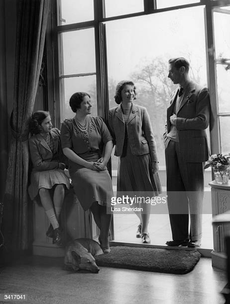 King George VI relaxes with his wife, the Queen Consort Elizabeth, and his children, Princesses Elizabeth and Margaret at the Royal Lodge, Windsor.