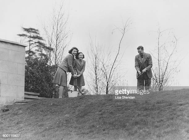 Princess Margaret Rose and Princess Elizabeth pumping water from a bucket as their father King George VI wields the hose in the grounds of the Royal...