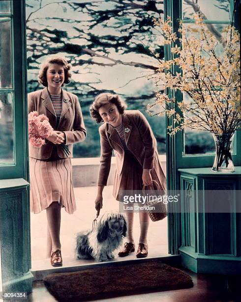 Princesses Elizabeth and Margaret Rose with one of their lhaso apso dogs outside the Royal Lodge, Windsor.