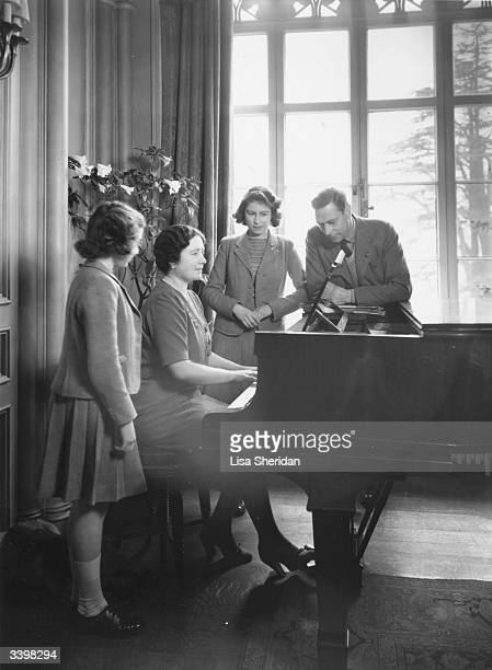 Queen Elizabeth playing the piano whilst Princesses Margaret Rose and Elizabeth and King George VI watch her at the Royal Lodge Windsor