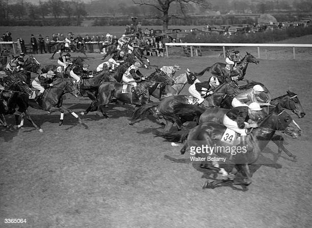A group of jockeys bunched together in the first furlong of the Lincoln racecourse