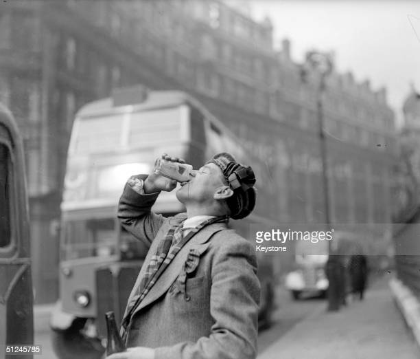 11th April 1947, A Scottish football fan wearing a bonnet and tartan scarf, drinking a glass of beer in London before an international match against...