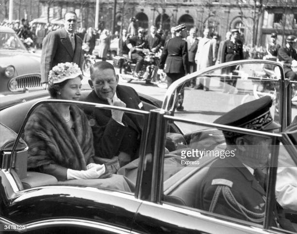 Queen Elizabeth II pays a visit to Paris and is accompanied on a tour of the city by French president Rene Jules Gustave Coty