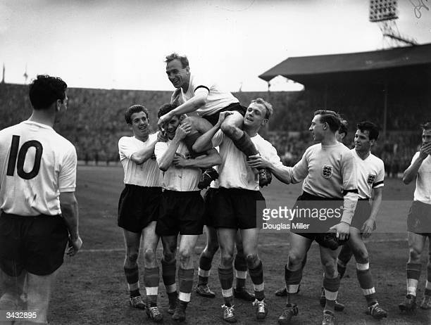 England and Wolverhampton Wanderers captain Billy Wright is carried aloft in triumph by his team mates following England's victory over Scotland at...
