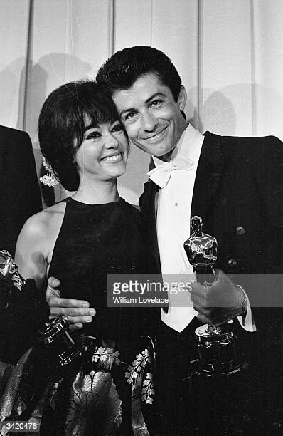 Actress and singer Rita Moreno and American actor George Chakiris both holding their Oscars at the award ceremony in Hollywood