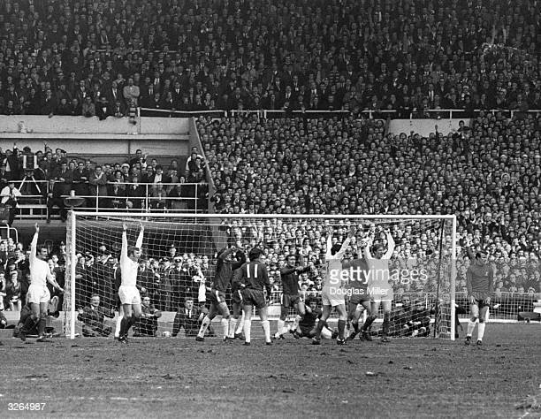 Jackie Charlton of Leeds United raises his arms in celebration after scoring his team's first goal from a corner during the FA Cup Final against...