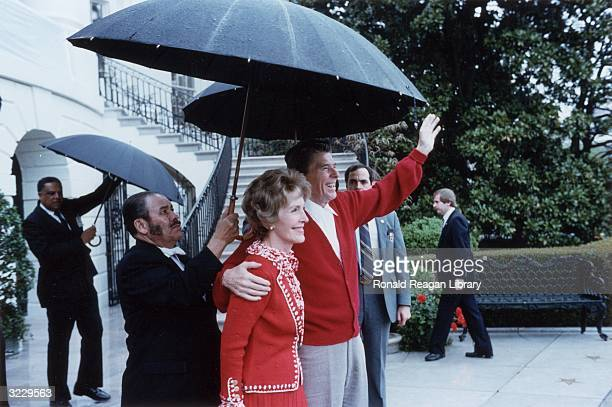 US President Ronald Reagan smiles and waves as he stands under an umbrella with First Lady Nancy Reagan after leaving George Washington Hospital...