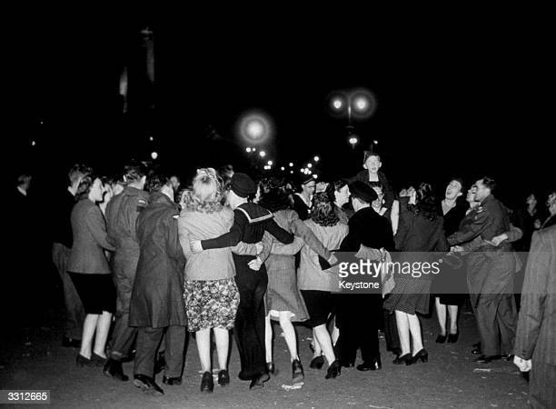 Revellers dancing in a floodlit Trafalgar Square to celebrate the end of the war in the Far East