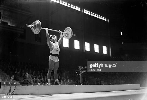 Harold Sakata of USA lifts a jerk of 314 lb at the 1948 Olympic Light Heavyweight Weightlifting in Earl's Court London bringing him in at second...