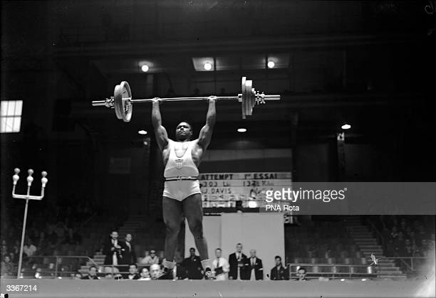 John Davis of USA takes part in the Super Heavyweight Weightlifting at the 1948 Olympic Games in London and comes in first with a load of 303 lb