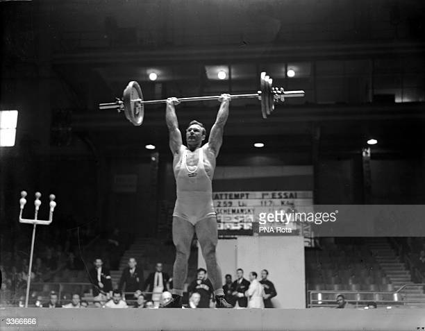 Norbert Schemansky of USA competes in the 1948 Olympic Super Heavyweight Weightlifting at Earl's Court London and comes in at second place with a...