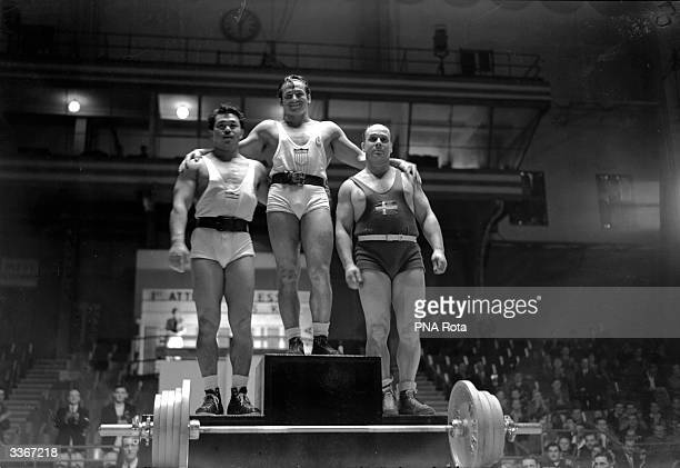 The three winners of the 1948 Olympic Light Heavyweight Weightlifting take their places on the podium in Earl's Court London The winner is Stanley...