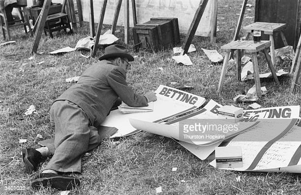 A bookie at the Brighton races writing up the odds Original Publication Picture Post 6050 The TwoLegged Race Goes Racing pub 1952