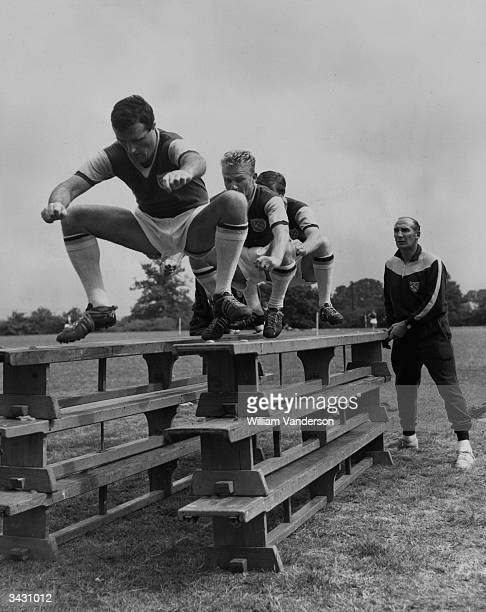 West Ham manager Ted Fenton watching three of his players Noel Cantwell Frank Grice and John Bond during a training session at Grange Farm Chigwell