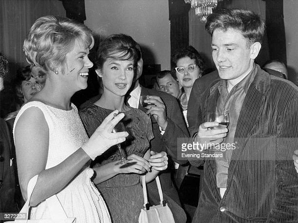 Young actor Albert Finney talks to his costars in Saturday Night and Sunday Morning Shirley Anne Field and Rachel Roberts at a social event in...