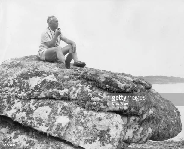 British Prime Minister Harold Wilson sitting quietly smoking his omnipresent pipe on a rock during his holiday to the Scilly Isles