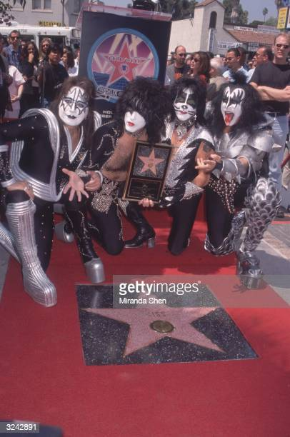 Four members of the American heavy metal music group KISS kneel on a red carpet while receiving their star on the Walk of Fame Hollywood California...