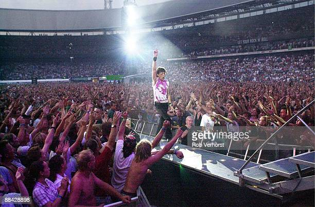 Mick Jagger from The Rolling Stones performs live on stage walking down gantry in arena/stadium with crowds/audience surrounding him during the Licks...