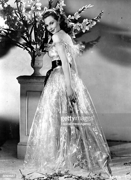 Hazel Court the red haired British leading lady wearing a dress made of cellophane with a large silk bow