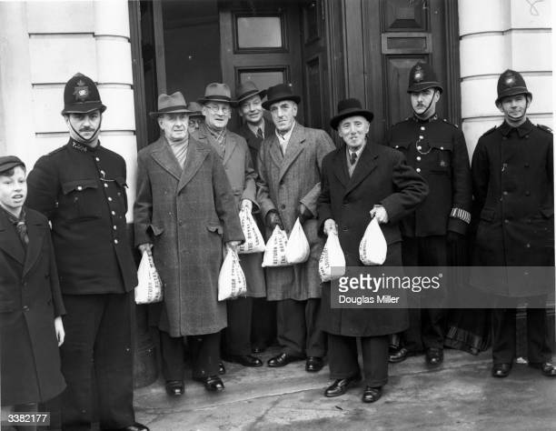 Policemen escorting officials of the West Green PSA Dividing Society from Barclays Bank before the society's annual shareout