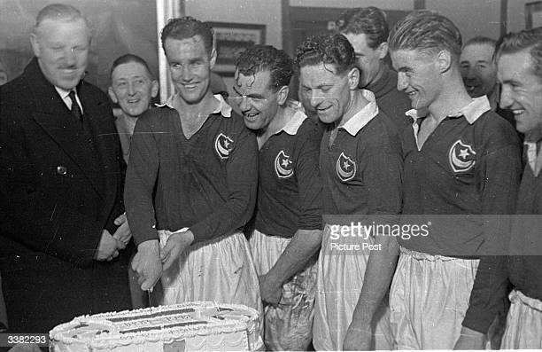Reg Flewin, captain of the Portsmouth football team, cuts the cake in the club boardroom in celebration of the club's golden jubilee. The team are...