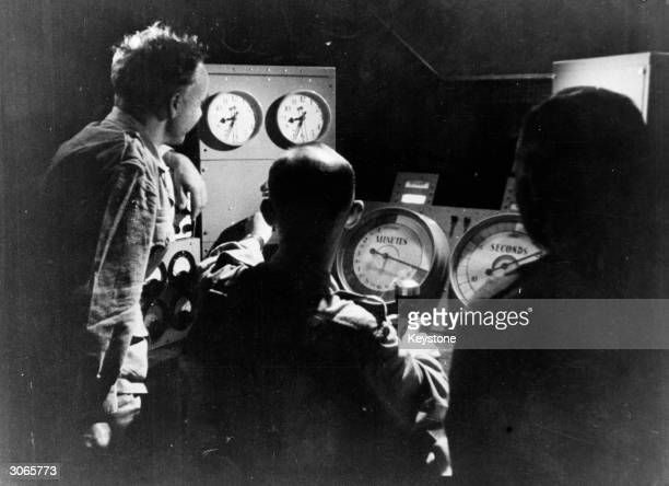 Scientists man the control panel on board the aircraft carrier 'Campania' during the testing of Britain's first atom bomb in the Monte Bello Islands...