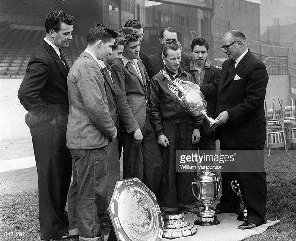 Manager Tom Whittaker and coach Leslie Compton showing some younger members of Arsenal the trophies which the club have won including the Football...