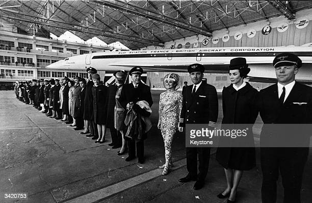 Pilots and hostesses from airliners which have ordered Concorde, the world's first supersonic airliner, stand in front of the plane at the official...