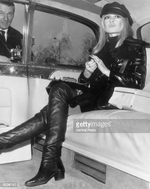 French actress Brigitte Bardot relaxes in the back of a limousine upon her arrival at London's Heathrow Airport. She has flown in from Paris to...