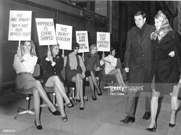 Secretaries sitting in office chairs on a London street holding placards which demand improvements in their working environment