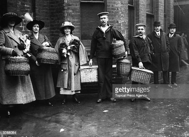 Competitors wait outside the Agricultural Hall for Crufts Dog Show as the Cross sisters on the left, arrive with arms and baskets full of Pekinese.