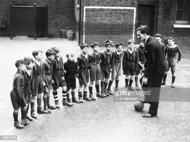 Mr D G Thomas the sports master at Pool's Park School in Finsbury Park London talks to the junior football team
