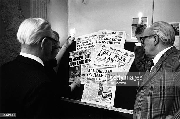 People in London using candles to read newspaper headlines about the continuing miners' strike Pay talks aimed at ending the fiveweek strike have...