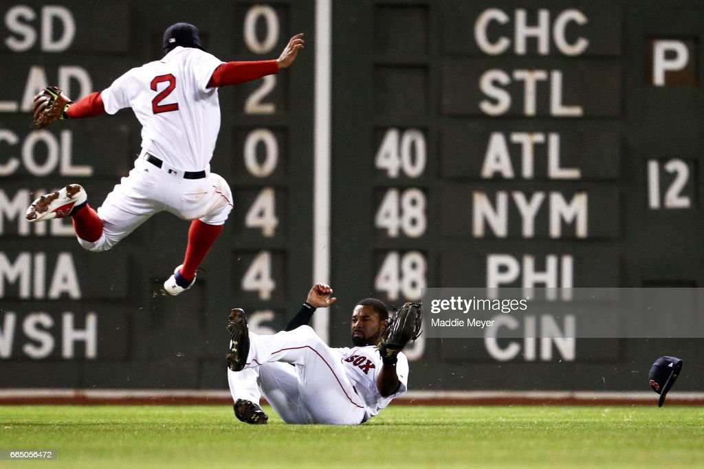 11th Jackie Bradley Jr. #19 of the Boston Red Sox slides beneath Xander Bogaerts #2 to catch a fly ball hit by Gregory Polanco #25 of the Pittsburgh Pirates during the eleventh inning at Fenway Park on April 5, 2017 in Boston, Massachusetts.