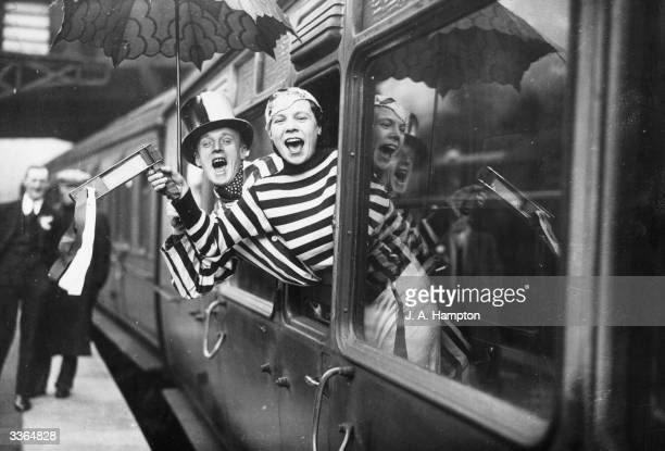 Arsenal football supporters cheer from the train carriage as they leave Paddington Station London on their way to Bristol for their team's FA Cup tie...