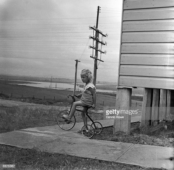 A young Australian girl rests on her tricyle