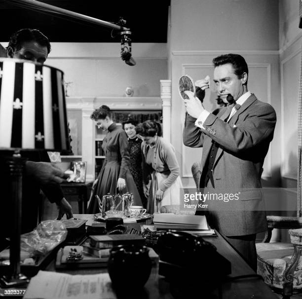 Irish actor Richard Todd applying his own make up on the set of 'Portrait of a Star' at Elstree The film's subject actress Janette Scott stands...