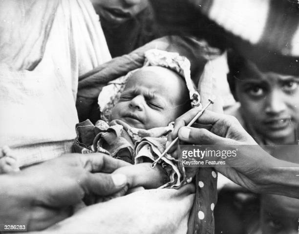 Baby is vaccinated against smallpox at an emergency clinic in Karachi during the worst epidemic of smallpox in Pakistan's history.