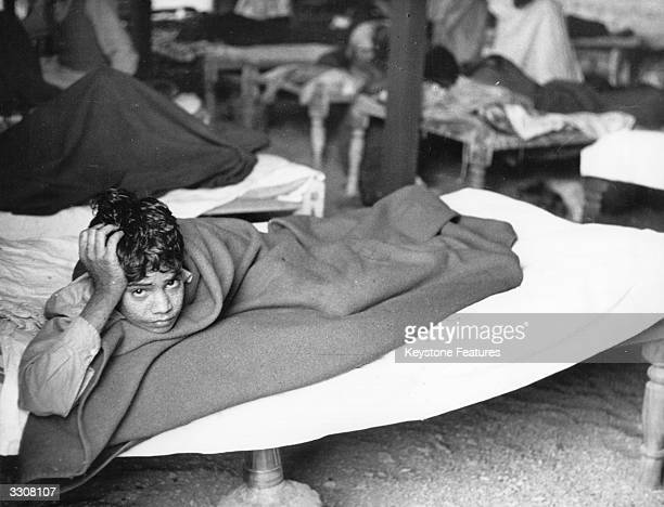 Young victim of smallpox lies in an overcrowded and ramshackle hospital at Karachi, during the worst epidemic of the disease in Pakistan's history.