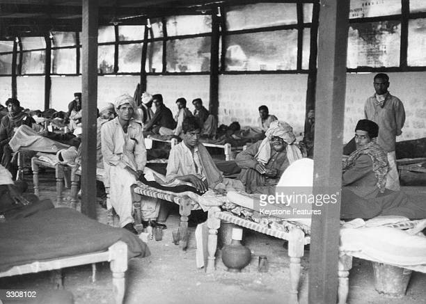 An overcrowded emergency smallpox ward in Karachi, with an earth floor, corrugated iron roof and rudimentary furnishings, during the worst outbreak...