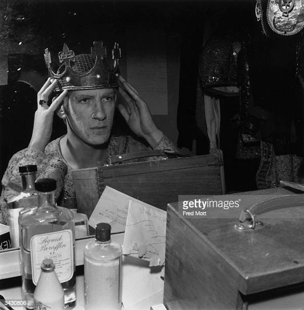 Actor David Warner of the Royal Shakespeare Company trying on a crown in his dressing room