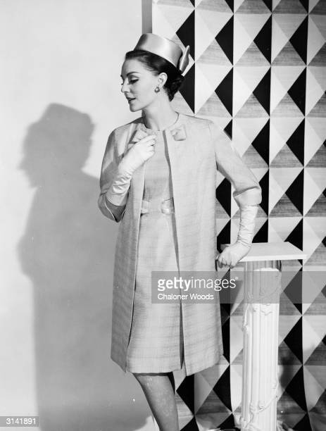 A lady in a matching dress and coat rests one elegantly gloved hand on a pedestal